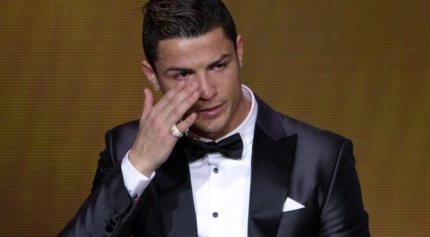 Real Madrid's Portuguese forward Cristiano Ronaldo cries after receiving the 2013 FIFA Ballon d'Or award for player of the year