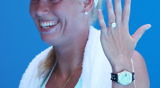 Caroline Wozniacki of Denmark shows off her engagement ring as she celebrates winning her first round match against Lourdes Dominguez Lino of Spain