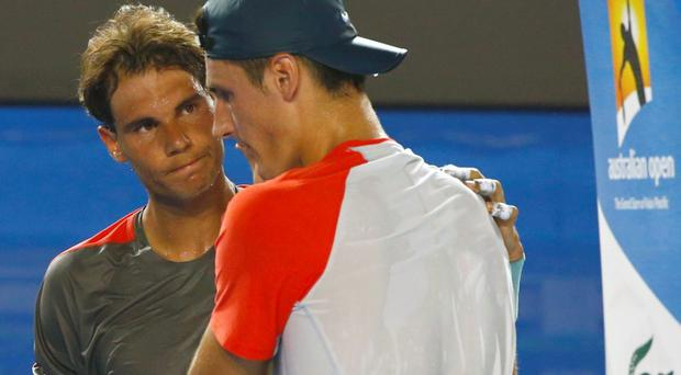 Rafael Nadal of Spain (L) comforts Bernard Tomic of Australia as he retires from their men's singles match at the Australian Open