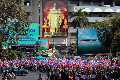 Anti-government protesters carry national flags as they march though central Bangkok