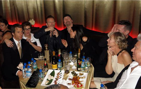 Men of the moment: U2, Bono's wife Ali Hewson and Larry Mullen Jr's other half Ann Acheson were joined by old friends Julia Roberts and Danny Moder at the Golden Globes after-party. (Photo: Splash)