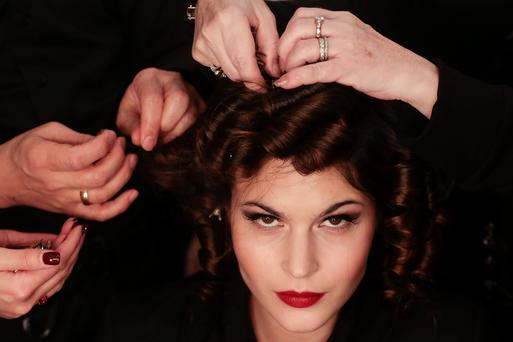 Model Lina Sandberg gets her hair prepared prior to the presentation of Lena Hoschek's Autumn Winter 2014 collection during the Mercedes Benz Fashion Week in Berlin, Tuesday, Jan. 14, 2014. (AP Photo/Markus Schreiber)
