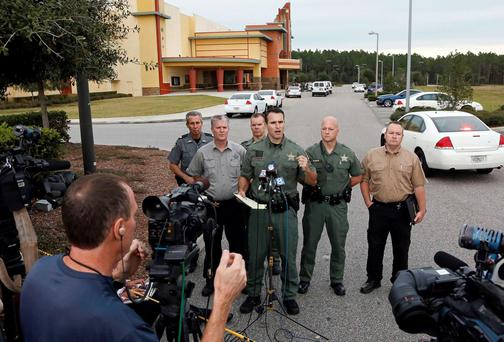 Pasco County Sheriff Chris Nocco speaks to the media as police tape surrounds the Cobb Grove 16 movie theater