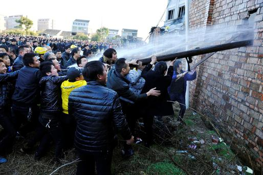 People try to break through the wall for firefighters to extinguish a fire at a factory in Wenling, Zhejiang province