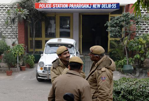 Indian policemen stand in front of the Paharganj police station in New Delhi