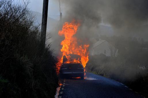 A man had a lucky escape when his car caught fire while driving outside Waterville in County Kerry on Wednesday. Photo shows another man, not the owner, calling the fire service for help. Picture by Don MacMonagle
