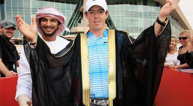 Rory McIlroy is presented with a traditional Emirate 'Bisht'
