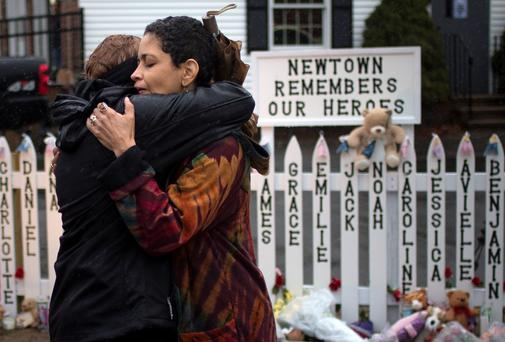 Women embrace at a memorial for the Sandy Hook tragedy in Connecticut in 2012