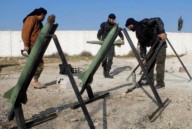 Rebel fighters prepare rockets to be launched towards forces loyal to Syria's President Bashar al-Assad in the eastern Damascus suburb of Ghouta
