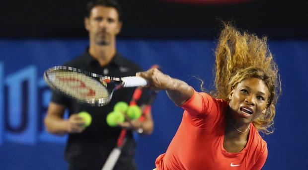 Serena Williams serves during a practice session as her coach Patrick Mouratoglou looks on
