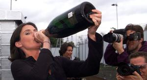 The runner-up of British TV company Channel 4's 'Big Brother' Anna Nolan, celebrates by drinking champagne as she poses for photographers on the set of the show on September 16, 2000. Photo: Reuters/Dan Chung.
