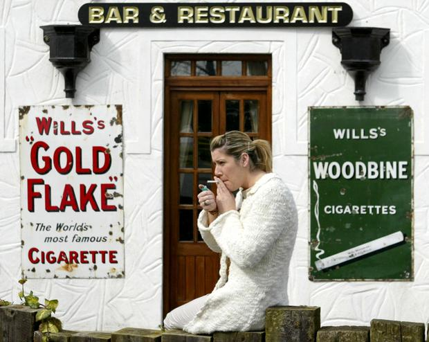 A woman smokes a cigaratte outside a County Louth bar after Ireland's smoking ban came into force. Photo: Reuters/Toby Melville.