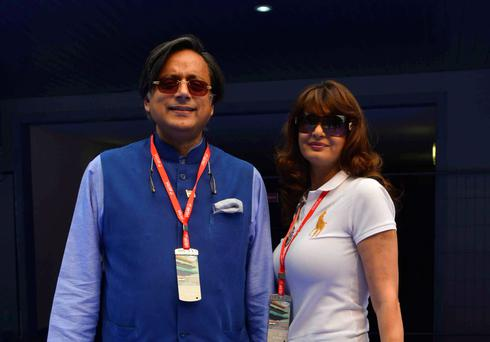 Sunanda Puskhar Tharoor (R), wife of India's Minister of State for Human Resource Development Shashi Tharoor, poses with her husband at the Indian F1 Grand Prix at the Buddh International Circuit in Greater Noida, on the outskirts of New Delhi, October 27, 2013.