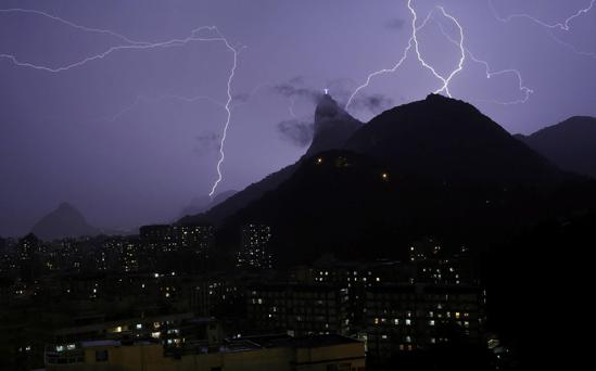 Lightning bolts strike through the sky near Christ the Redeemer statue in Rio de Janeiro, Brazil