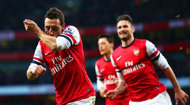 Santi Cazorla of Arsenal (L) celebrates with Olivier Giroud (R) as he scores their first goal during the Barclays Premier League match between Arsenal and Fulham at Emirates Stadium.