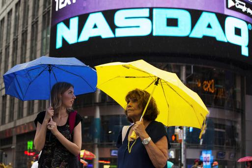 Two women hold umbrellas as they walk past the Nasdaq