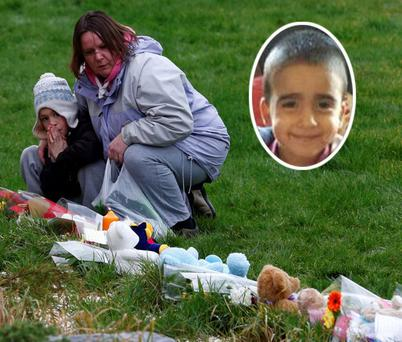 A mother and child look at floral tributes and soft toys left near the home of three-year-old Mikaeel Kular (inset) in Edinburgh