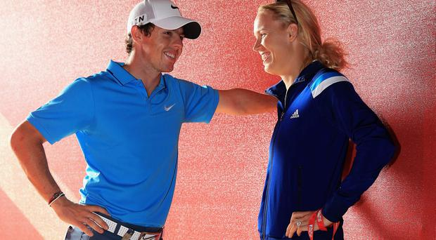 Rory McIlroy of Northern Ireland talks to his fiance Caroline Wozniacki of Denmark