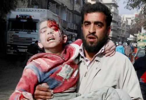 A man carries a wounded child after what activists said was an air strike by forces loyal to Syria's president Bashar Al-Assad in the Al-Maysar neighborhood of Aleppo January 19, 2014. Photo: Reuters