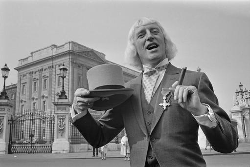 Jimmy Savile showing off his OBE after his investiture at Buckingham Palace, London, 21st March 1972. Photo: Getty.