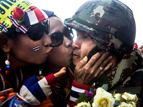 Anti-government demonstrators kiss a soldier after Thai security personnel stationed in the Government house agreed to leave following discussions between the army and protesters, in Bangkok