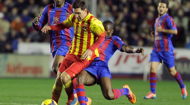 Barcelona's Lionel Messi (C) is tackled by Levante's Pape Diop