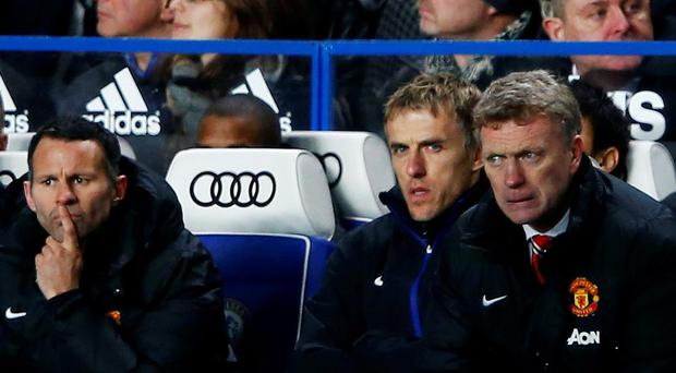 Manchester United manager David Moyes (R) watches from the bench with Phil Neville and Ryan Giggs