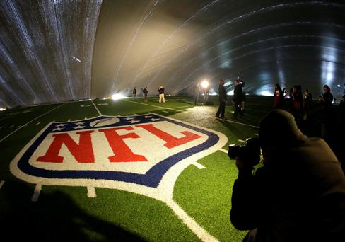 The NFL logo at midfield of MetLife Stadium is illuminated by lights on television reporters' videocameras as members of the media are given a tour under a tarp used by crews to keep the turf dry ahead of Super Bowl XLVIII