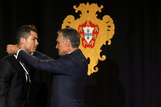 Portuguese President Anibal Cavaco Silva, right, decorates Portugal's soccer team captain Cristiano Ronaldo with the Ordem do Infante Dom Henrique, Order of Prince Henry, Monday, Jan. 20 2014, at the Belem presidential palace in Lisbon. (AP Photo/Andre Kosters, Pool)