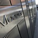 Pedestrians walk past the Moody's Investors Service Inc. logo displayed outside of the company's headquarters in New York, U.S