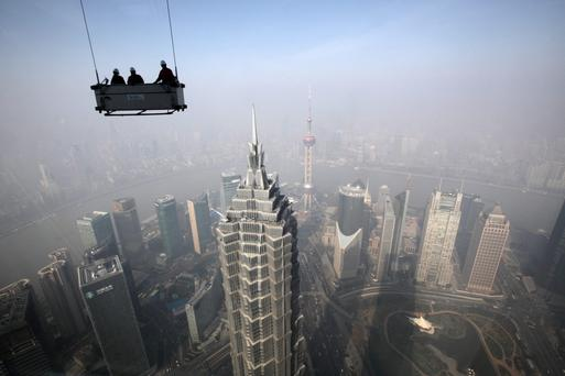 Workers stand in a suspended platform ready to clean windows at the Shanghai World Financial Center in the Pudong area of Shanghai. Photographer: Tomohiro Ohsumi/Bloomberg...I