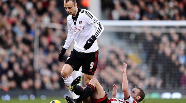 Sunderland's Lee Cattermole and Fulham's Dimitar Berbatov battle for the ball during the Barclays Premier League match at Craven Cottage, London.