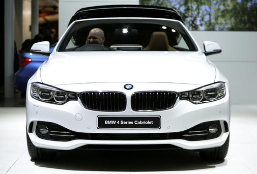 An attendee sits in the driver's seat of a BMW4 Series Cabriolet vehicle at the 43rd Tokyo Motor Show 2013.