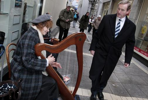 Taoiseach Enda Kenny chats with street musician Brenda Molly after attending mass in Dublin city centre yesterday