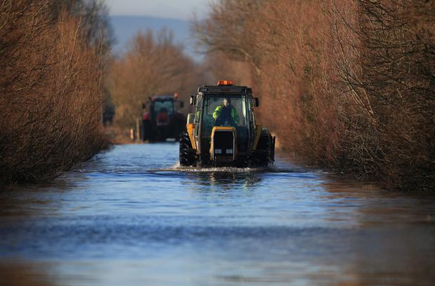 A tractor drives through flood water still blocking the A361 between East Lyng and Burrowbridge on the Somerset Levels near Langport on January 20, 2014 in Somerset, England. Photo by Matt Cardy/Getty Images