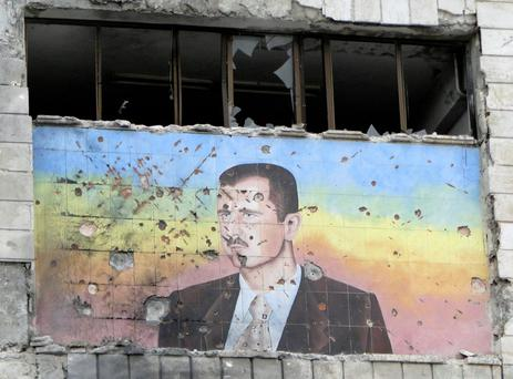 Mural of Syria's President Bashar al-Assad riddled with holes on the facade of the police academy in Aleppo, after it was captured by Free Syrian Army