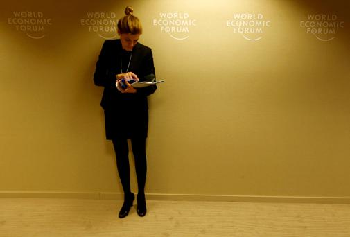 A participant takes a break between sessions during the annual meeting of the World Economic Forum (WEF) in Davos