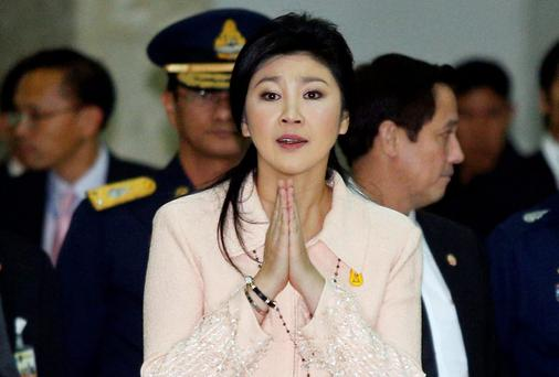 Thailand's Prime Minister Yingluck Shinawatra gestures while speaking to reporters following following the declaration of a state of emergency in Bangkok