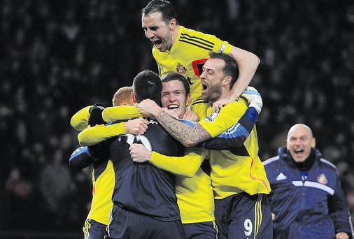 Sunderland captain is top of the pile as they celebrate their shootout victory against Manchester United last night