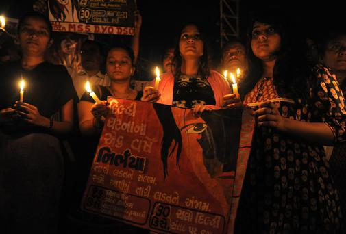 Indian students and activists at a memorial for a gang-rape and murder of a 23-year-old physiotherapy student that sparked massive protests in the Indian capital, outside Vastrapur Lake in Ahmedabad