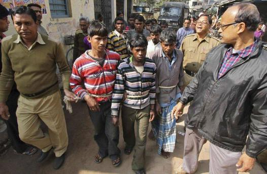 Indian police escort men accused of the attack to court. 13 men have been arrested and remain in custody.