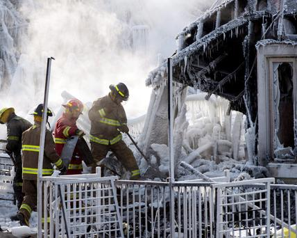 Rescue personnel search through icy rubble of fire that destroyed a seniors' residence