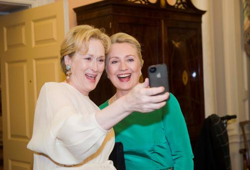 Actress Meryl Streep uses her IPhone to take a photo of her and Hillary Clinton.
