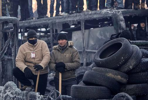 Anti-government protesters stand on a barricade at the site of clashes with riot police in Kiev. Reuters