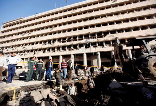 Rescue workers are seen with an excavator in front of the Cairo Security Directorate after a bomb attack, in downtown Cairo. Reuters