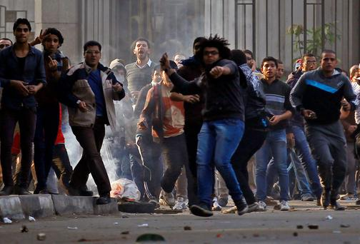 Anti-government protesters and members of the Muslim Brotherhood throw stones and glasses during clashes with supporters of Egypt's army and police at Ramsis street