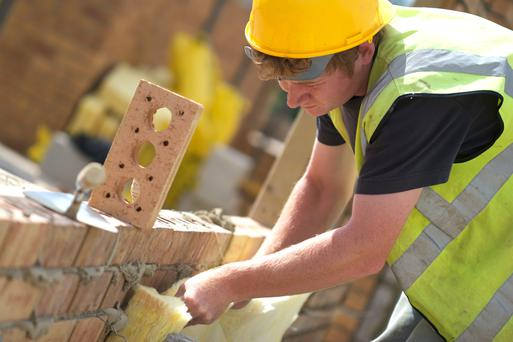 A bricklayer fitting insulation to a newly built wall - cost saving insulation measures can be installed to older houses.
