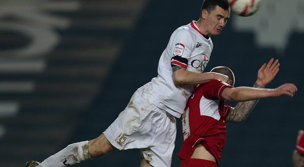 Shaun Williams of MK Dons rises above James Collins of Swindon Town to head the ball during the npower League One match between MK Dons and Swindon Town