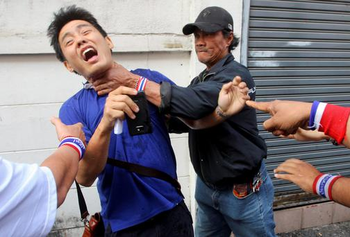Anti-government protesters attacked a voter near a polling station in Bangkok last week. Protesters surrounded almost half of the polling stations in Bangkok, election officials said, chaining doors shut and forcing the cancellation of advance voting in many centres for a disputed election on Sunday. Reuters