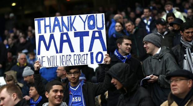 A Chelsea fan holds a placard in recognition of Spanish midfielder Juan Mata, who just signed to join Manchester United